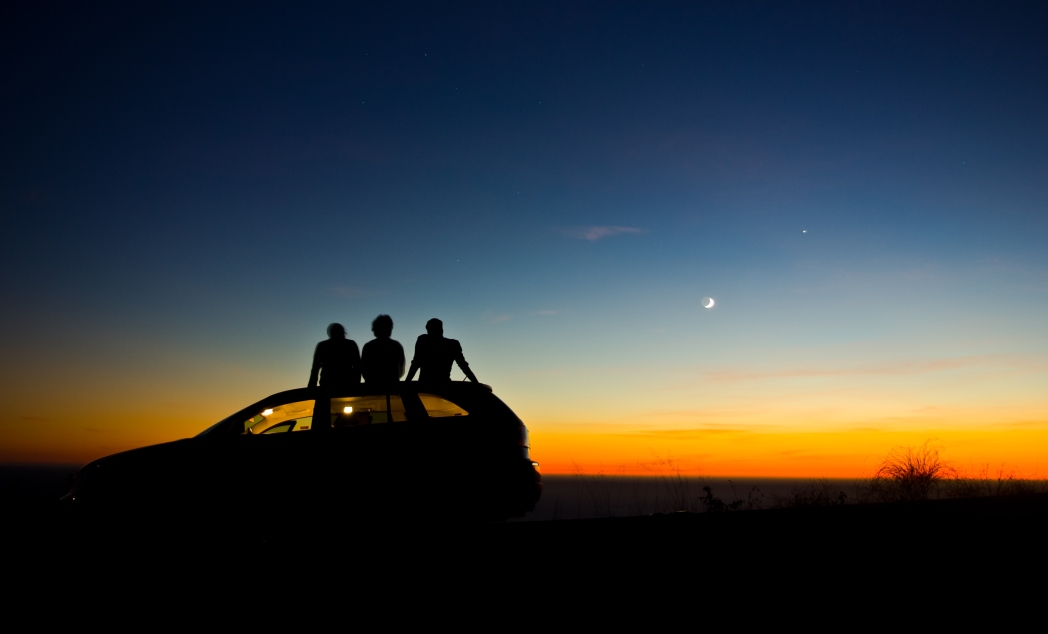 Trio on the roof of the car enjoying the sunset