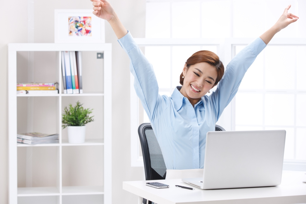 Woman sitting in front of a laptop and raising her hands in celebration.