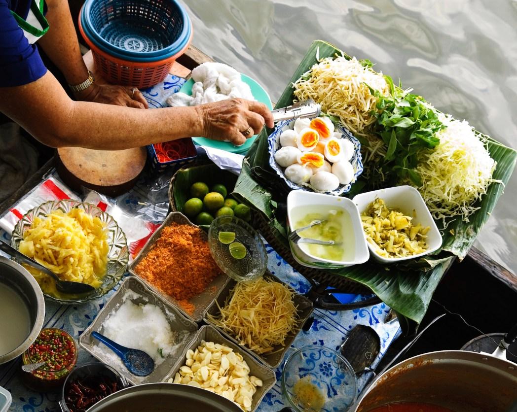 Vendor serving noodles on a boat