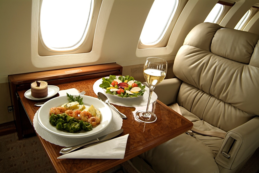 Plush business class seat with a fancy meal laid out.