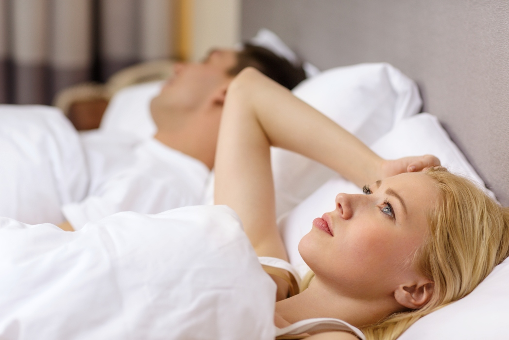 Woman awake in bed while her partner sleeps beside her.