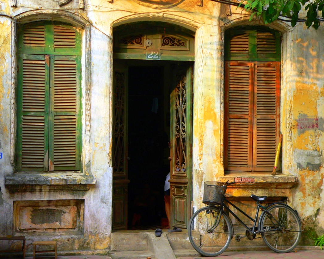 Old house with shutters and bike propped against wall