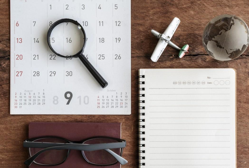 A calendar, journal, and model airplane arranged on a desk.
