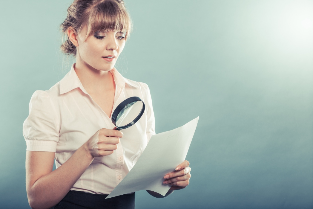 A lady looking at a piece of paper with a magnifying glass