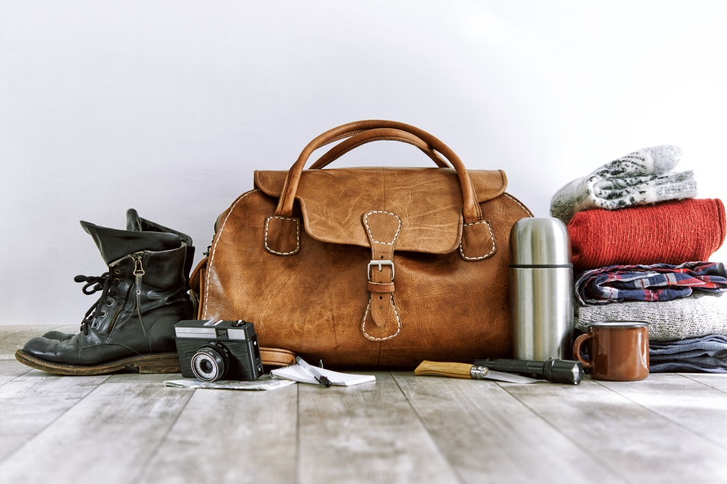bag surrounded by items like boots, camera and clothes