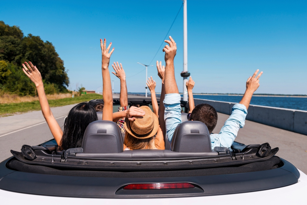 Group of friends in an open-top car with their arms in the air