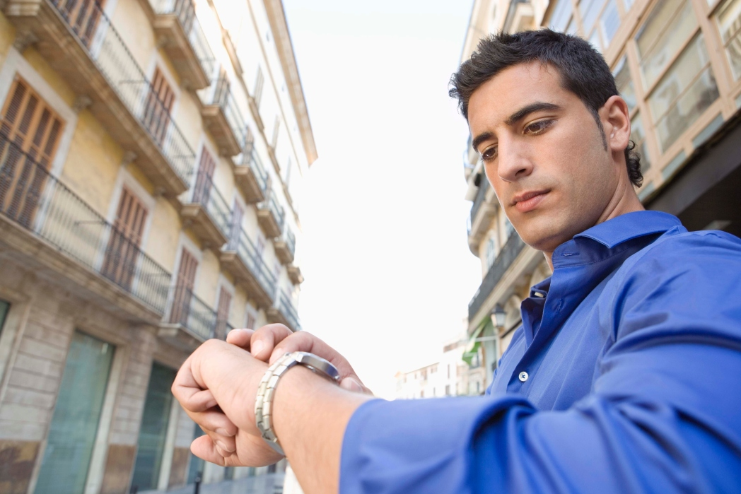 Man checking his watch while standing in the street.