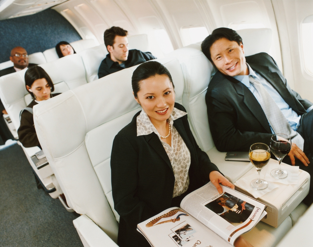 One male and one female passenger sitting in business class, smiling and reading magazines.