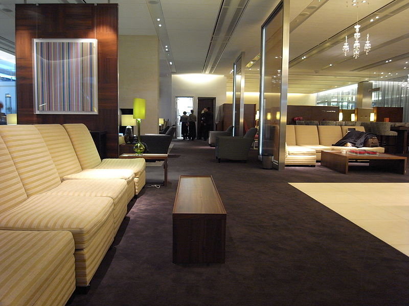 Beige sofas line the left side of this sleek fully-carpeted British Airways lounge