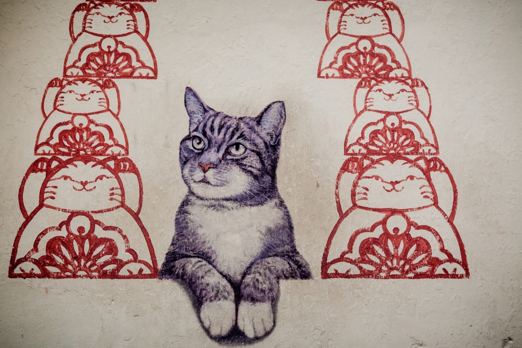 Painting of a cat with fortune cats surrounding it