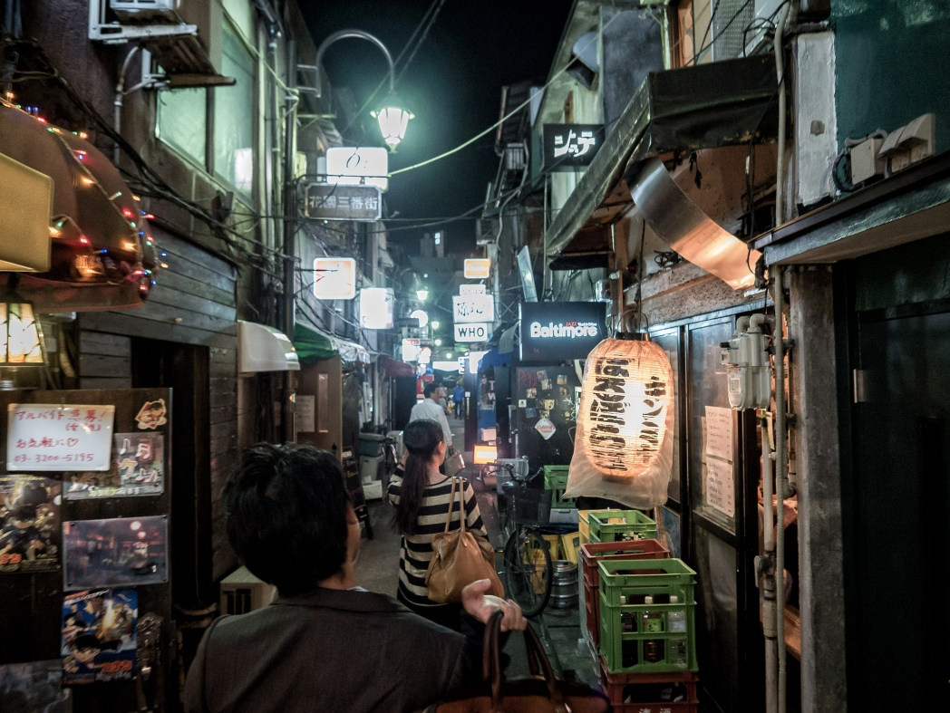 Narrow alleyway with small wooden-faced Japanese bars and a couple of people browsing