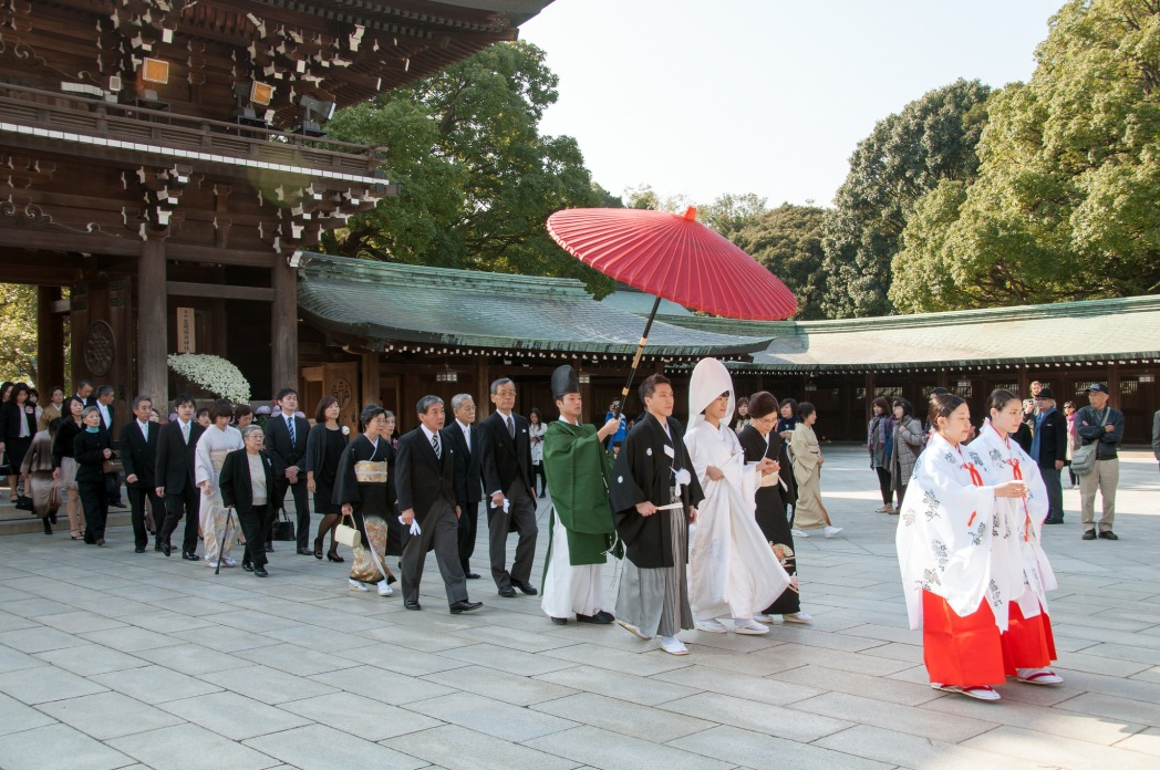 Traditional wedding procession at shrine with bride and groom being led out of shrine