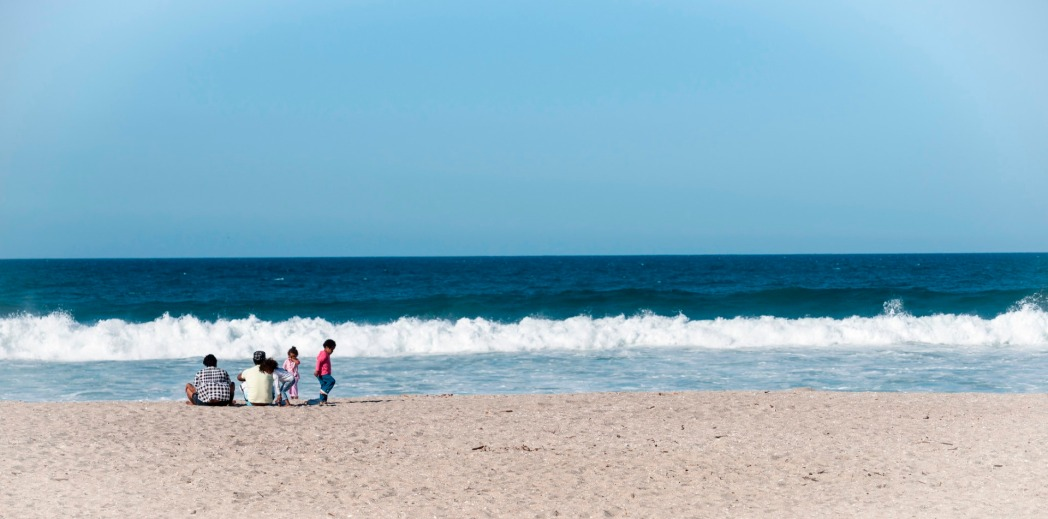 A family sitting on the sand, watching waves coming in