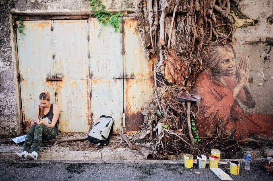 Artist sitting beside a painted old lady