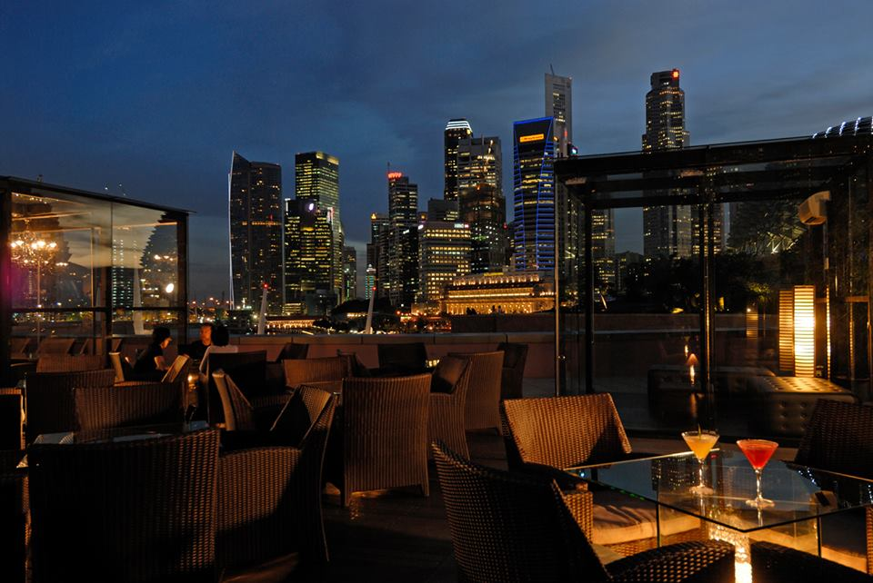 Rooftop bar with illuminated skyline in the background.