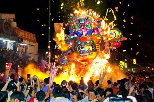 The burning of paper effigies and joss sticks on a street in Penang