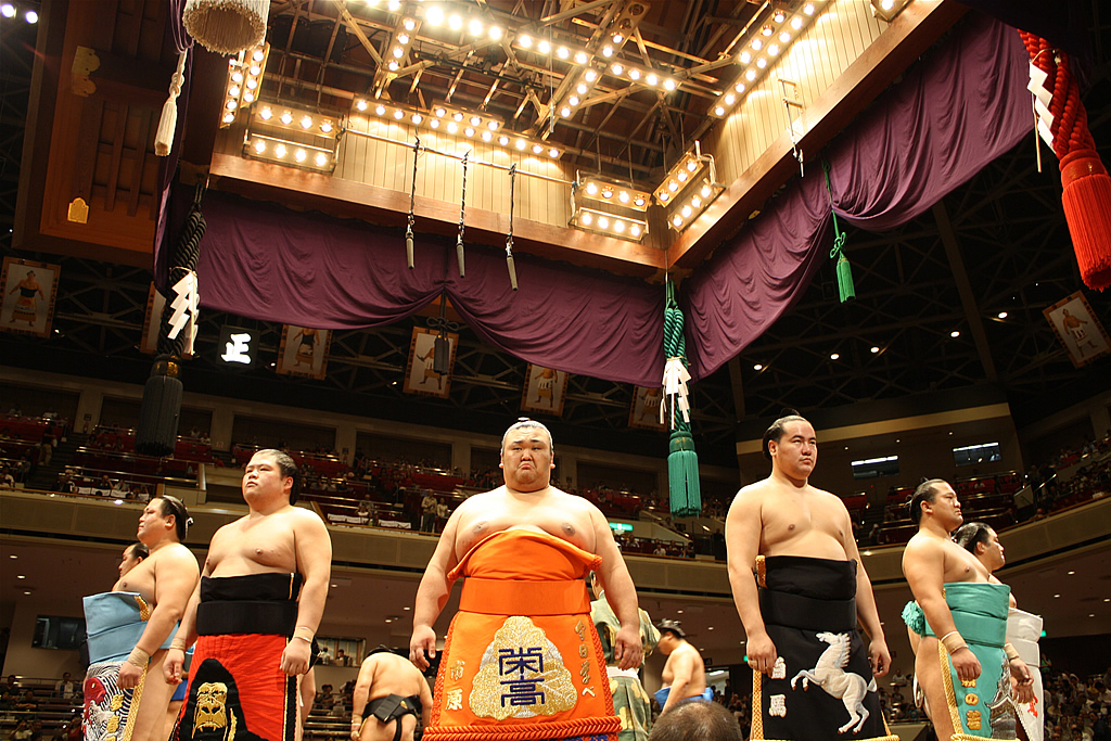 Sumo wrestlers lined up and facing the audience in a competition hall