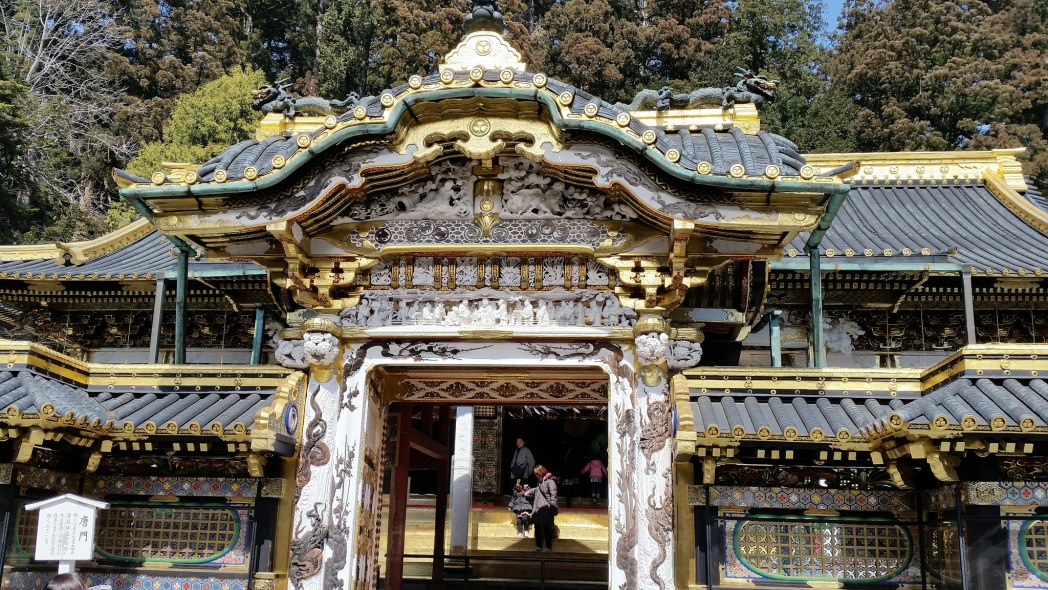 The weathered but still standing gateway to the shrine is embellished with intricate green, gold, and white details.