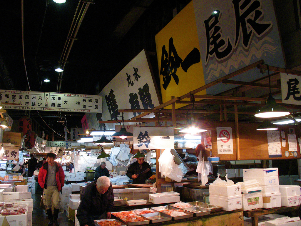 Shot of fish market stalls with vendors and signs with Japanese characters in the background