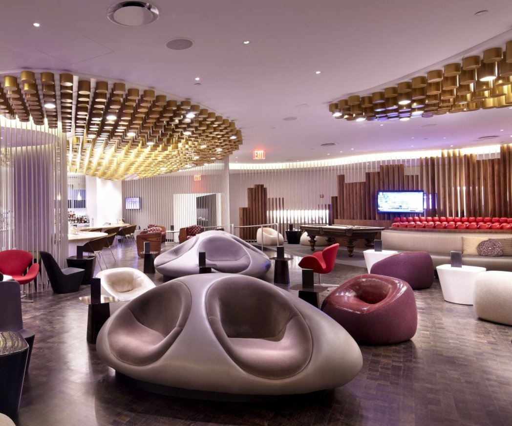 Space-age chic seating with gold lighting in the ceiling of Virgin Atlantic Club of John F. Kennedy Airport